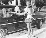 Woman delivering cotton candy to a car sometime in the 1950s