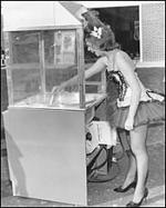 Woman working a popcorn or cotton candy machine sometime in the 1950s